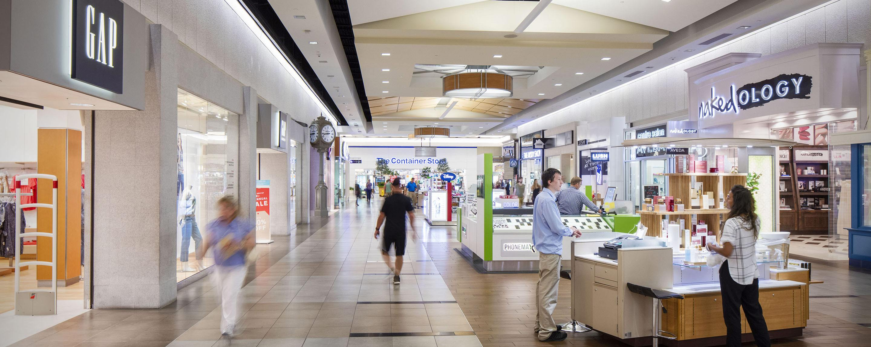 People shop among the shops and kiosks of an indoor mall. Storefronts include Lush and Gap
