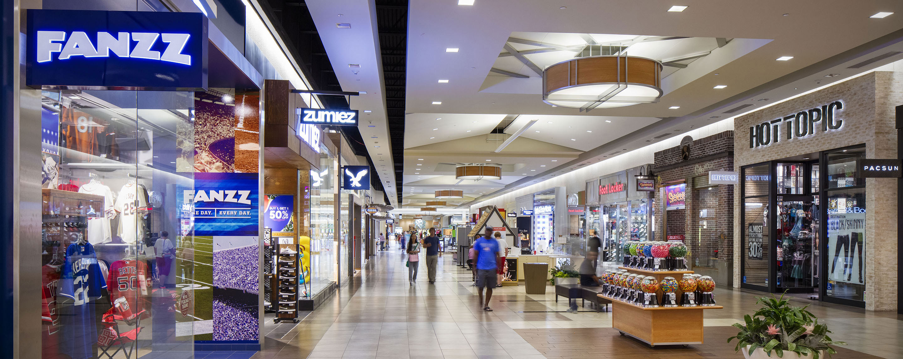 A line of stores stand in an indoor mall. Several brands are visible, including Fanzz and Hot Topic