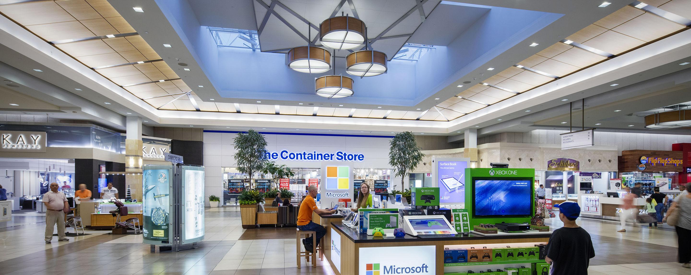People shop in a mall near kiosks and stores such as Zagg, Breitling, and The Container Store.