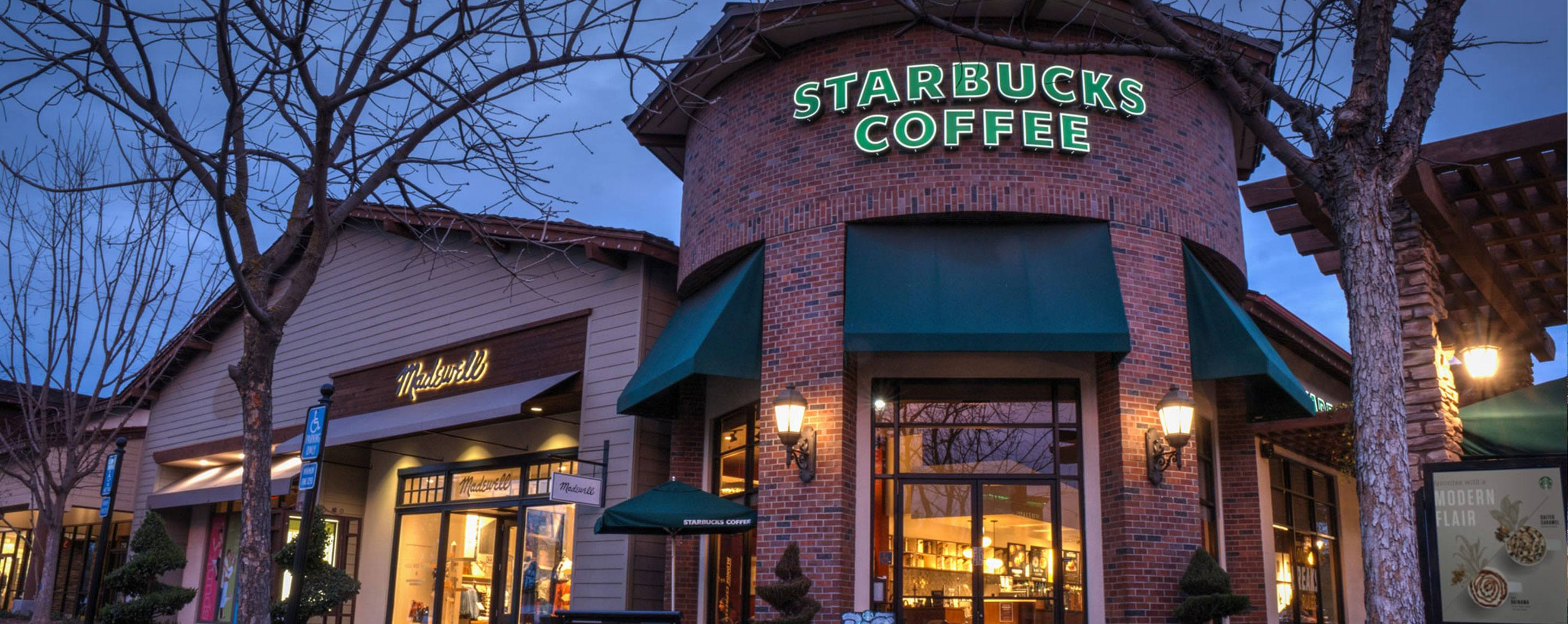 A shot of the exterior of a Starbucks at twilight. The Starbucks is well lit and made of bricks.