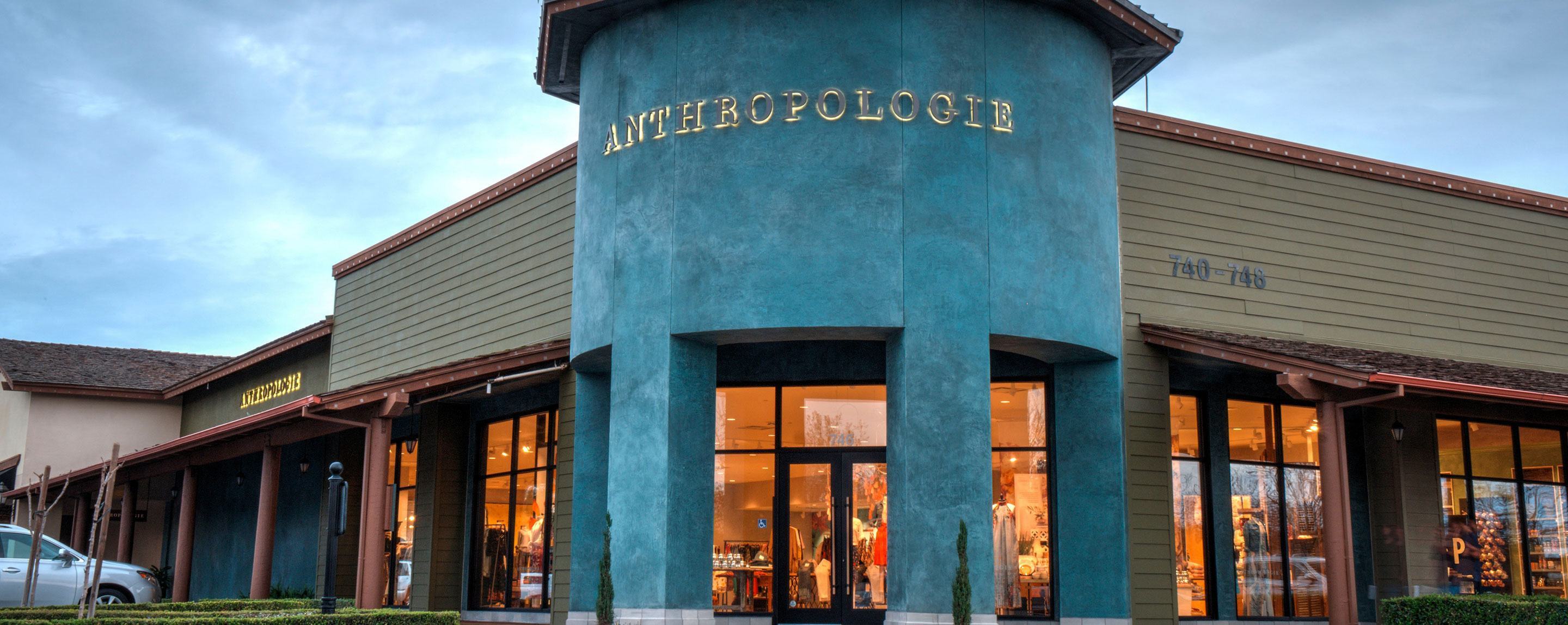 A blue-painted Anthropologie store is located in a corner location of an outdoor shopping plaza on an overcast day.