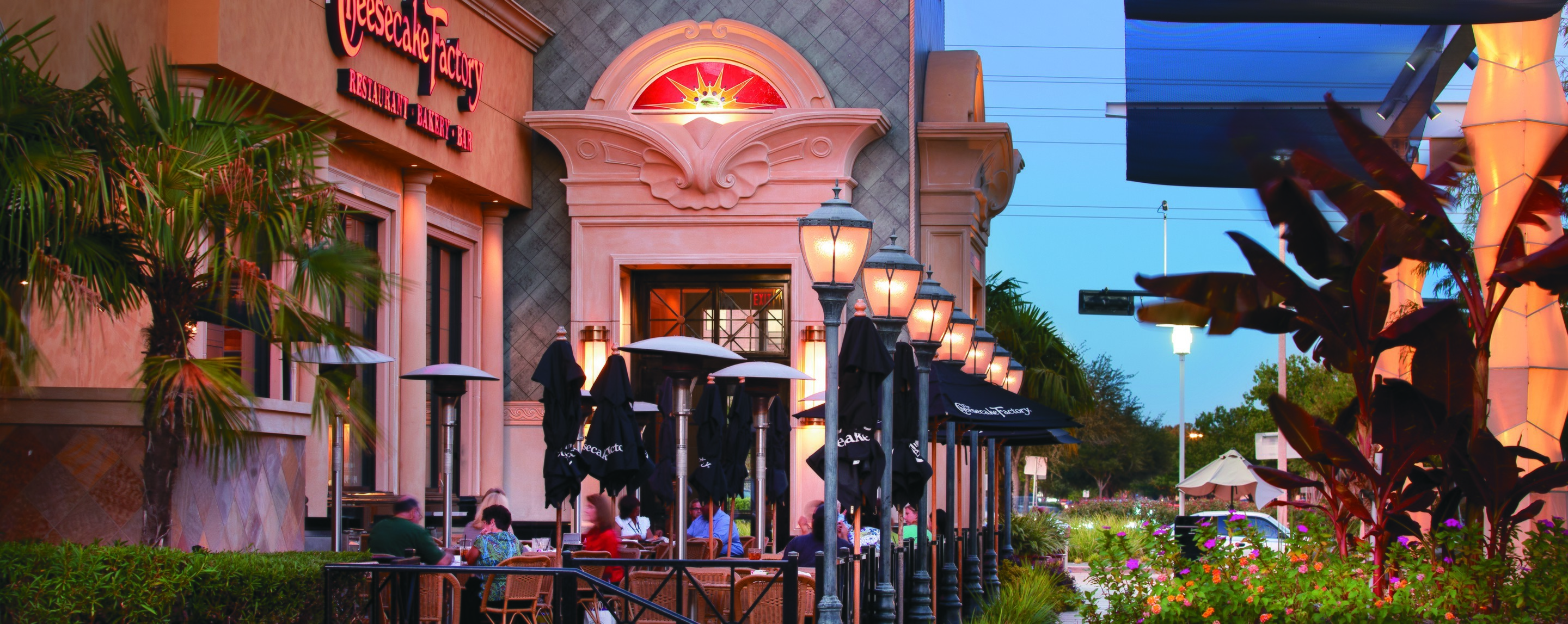A crowded restaurant's patio seats customers outdoors near a fountain and another building.