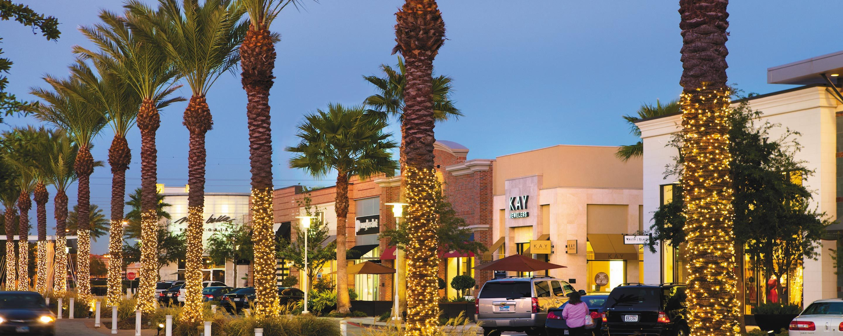 A line of palm trees with Christmas lights stands in front of the exterior of a large mall.