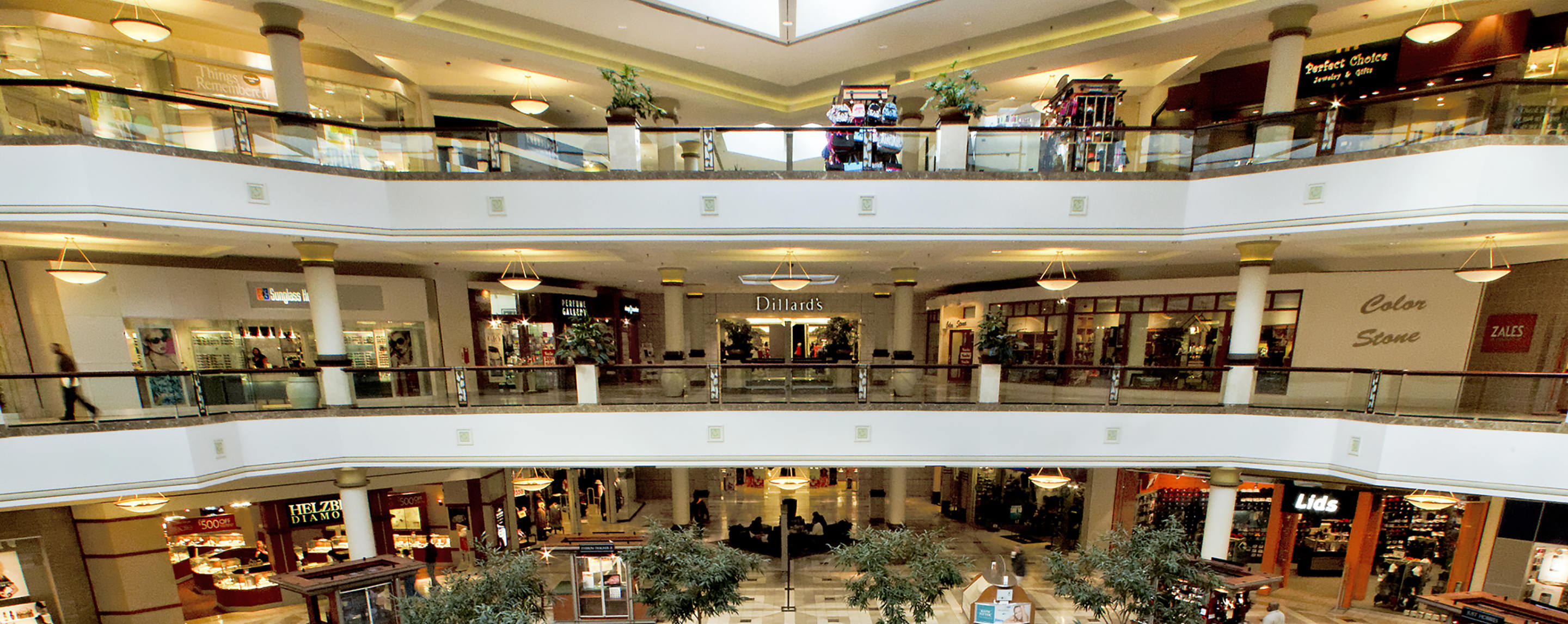 Stores such as Dillard's, Lids, and Zales can be seen on the halls of a three storied shopping mall.