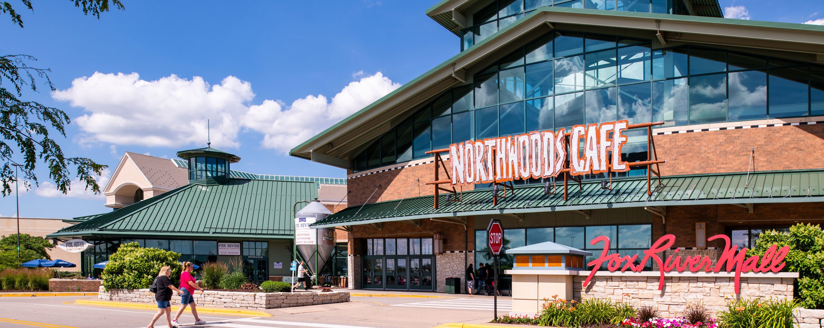 An outside shot of Northwoods Cafe on a sunny day. A couple is walking towards the entrance.