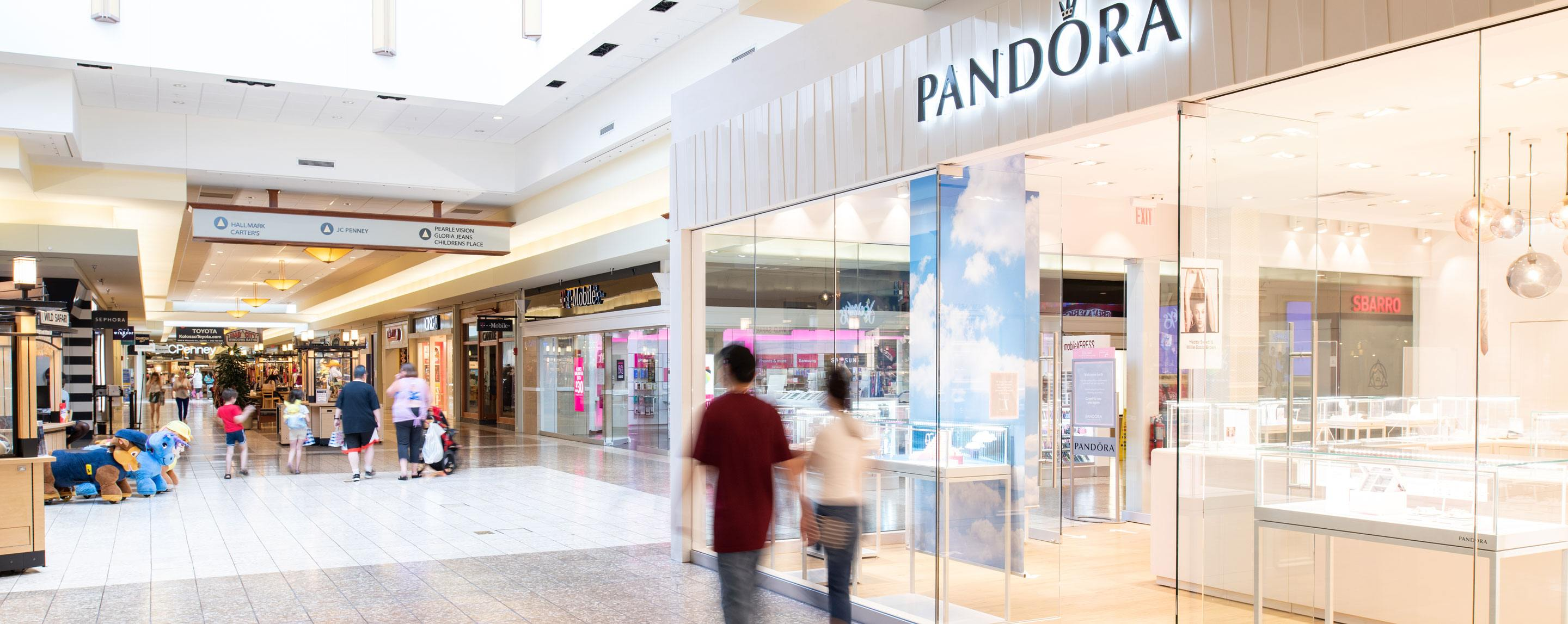 People walk down an indoor mall. Several storefronts are visible, including Pandora.