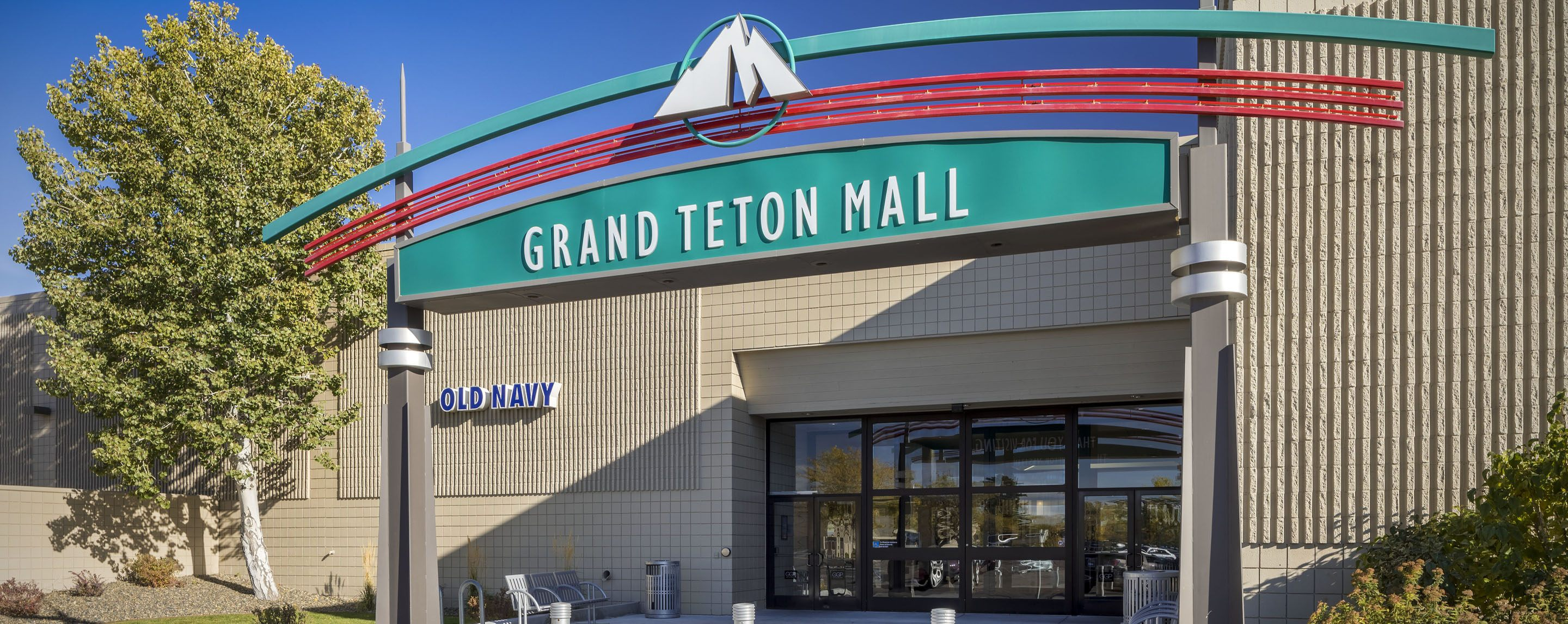 The blue sign for an Old Navy store can be seen on the building near the entrance for the Grand Teto
