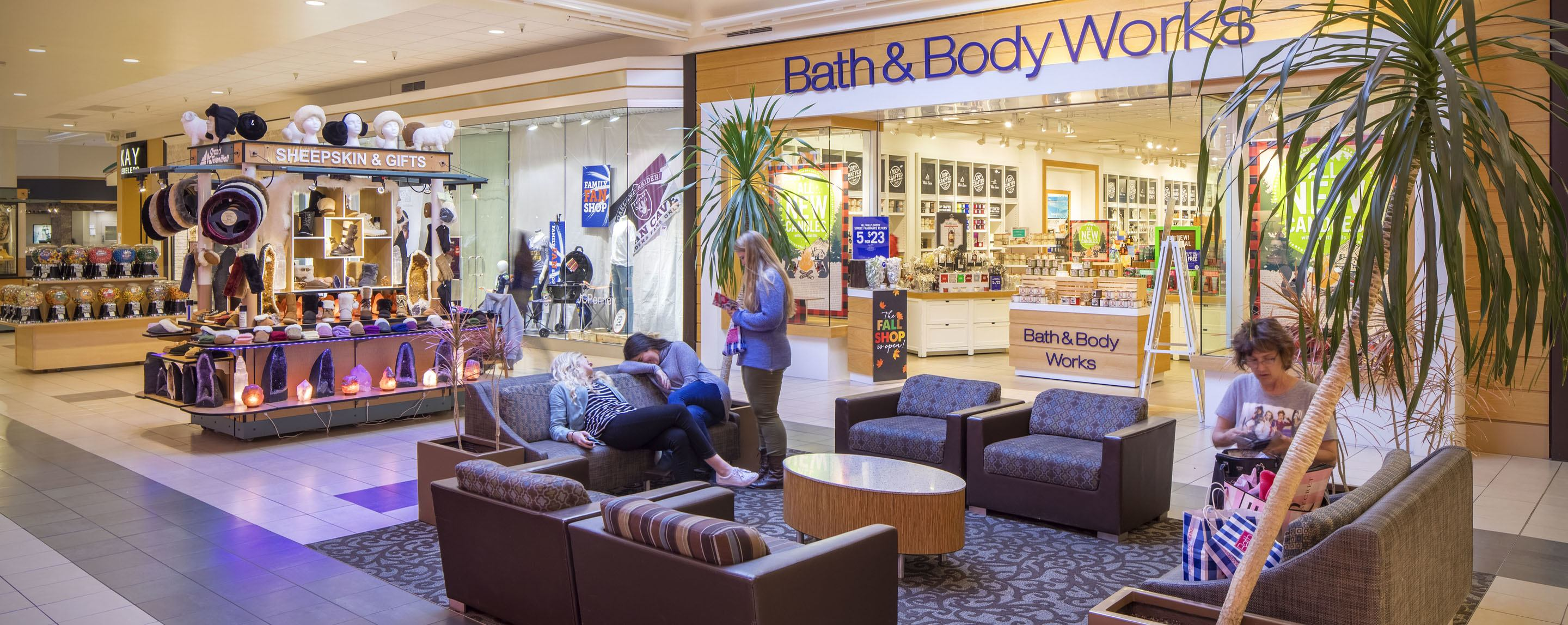 Next to a kiosk, people sit on couches outside of a Bath and Body Works in an indoor mall.