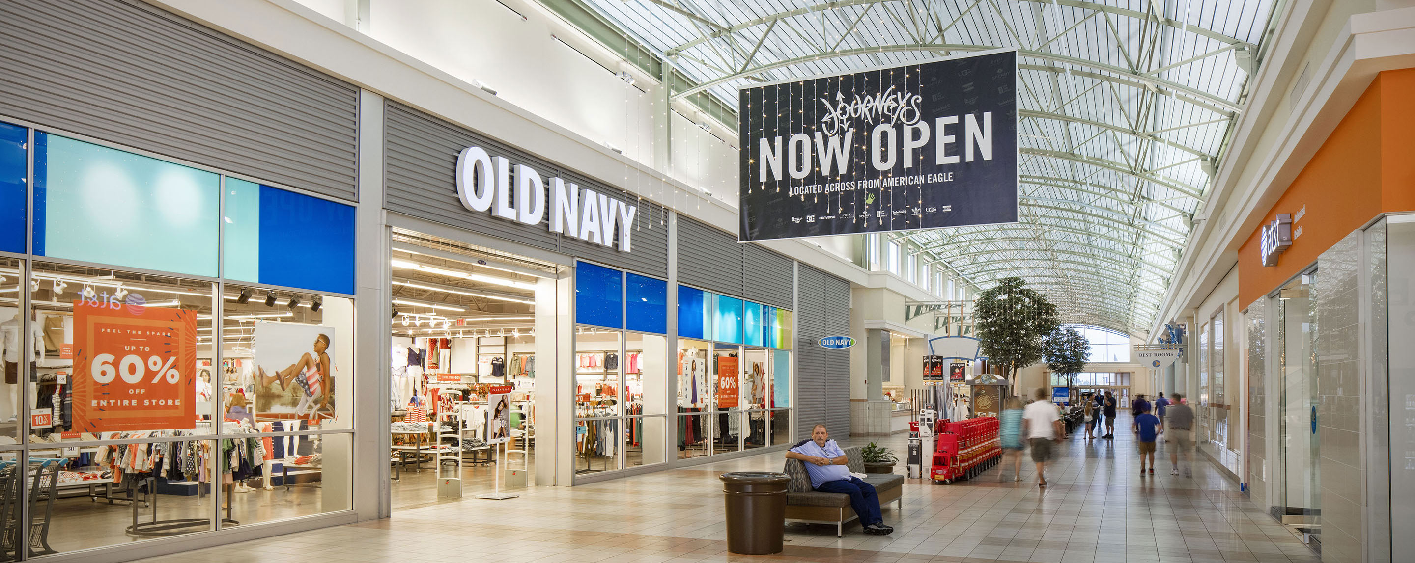 """A black """"Now Open"""" sign for Journeys hangs above a seated man and outside of an Old Navy."""