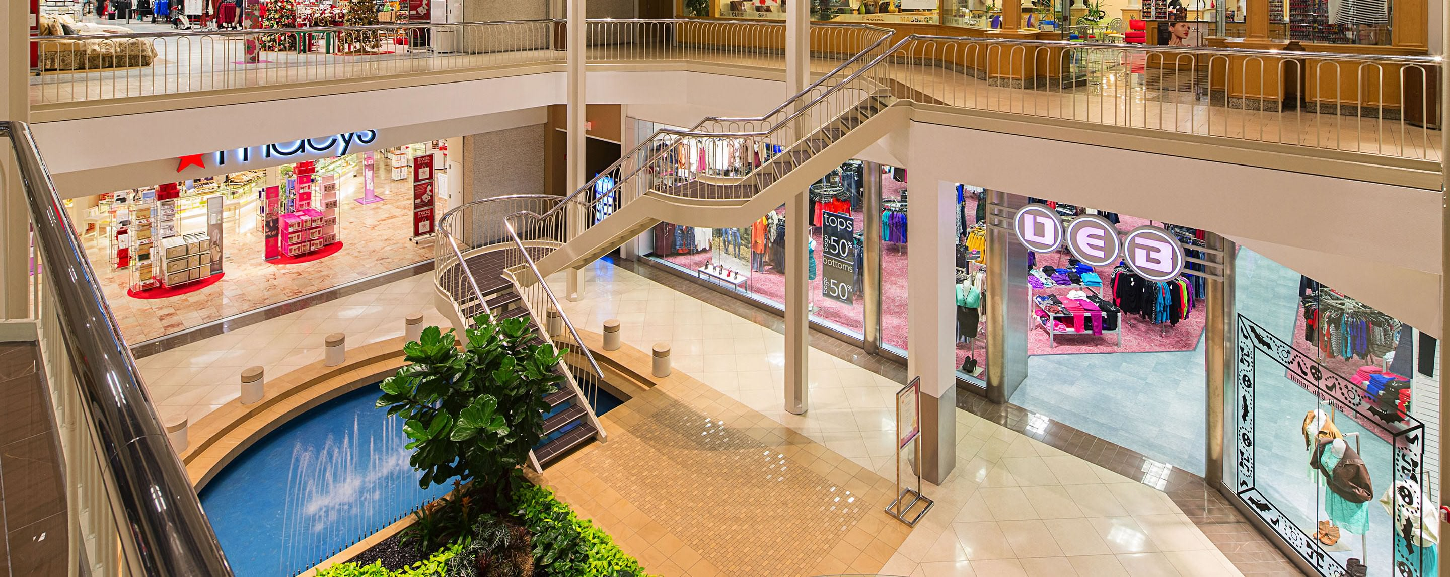 A second story shot of a staircase in the Hulen Mall. A Macy's storefront stands on the first floor.