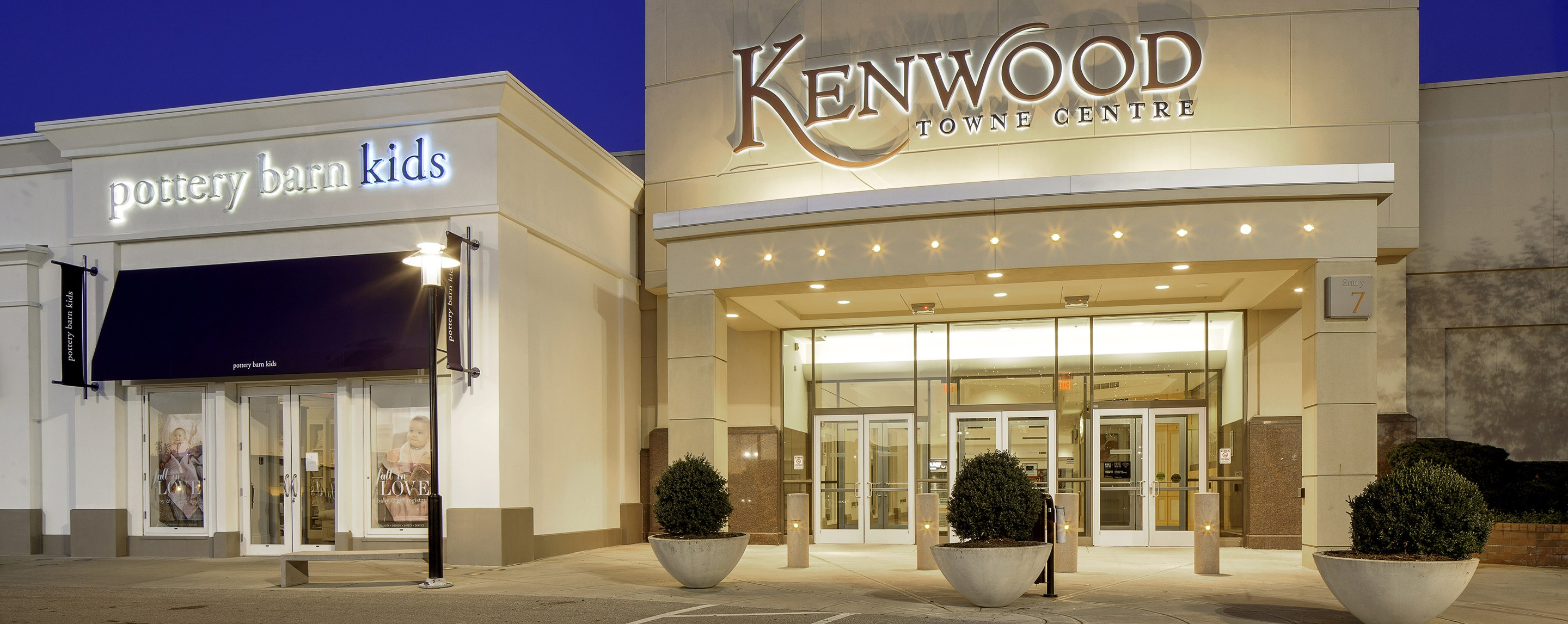 A store front with glass doors with a sign that says Kenwood Towne Centre and a pottery barn kids next door.