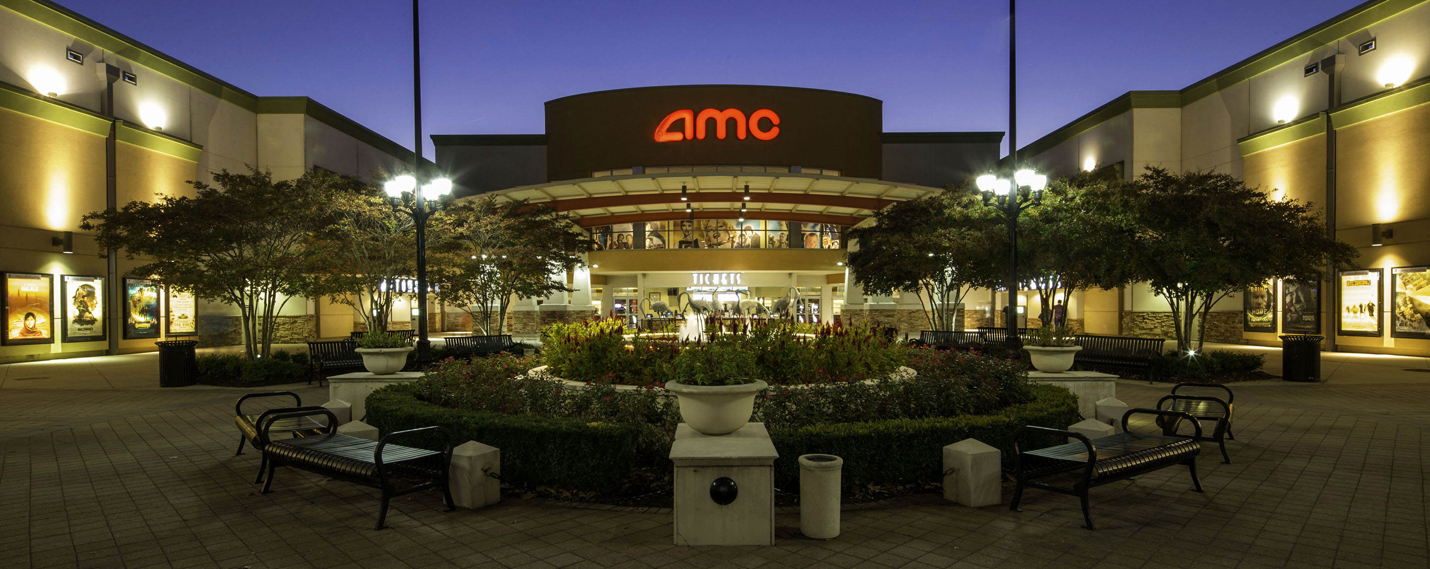 A courtyard with benches is in front of a large building that says amc on the front.