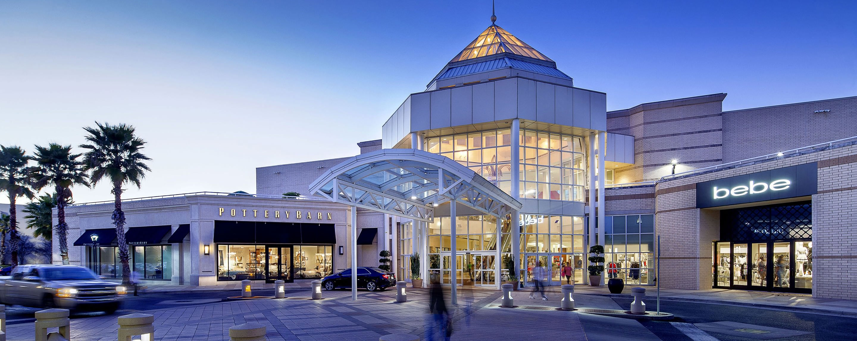 An exterior of a mall is well lit at twilight. A Bebe and a Pottery Barn are visible.