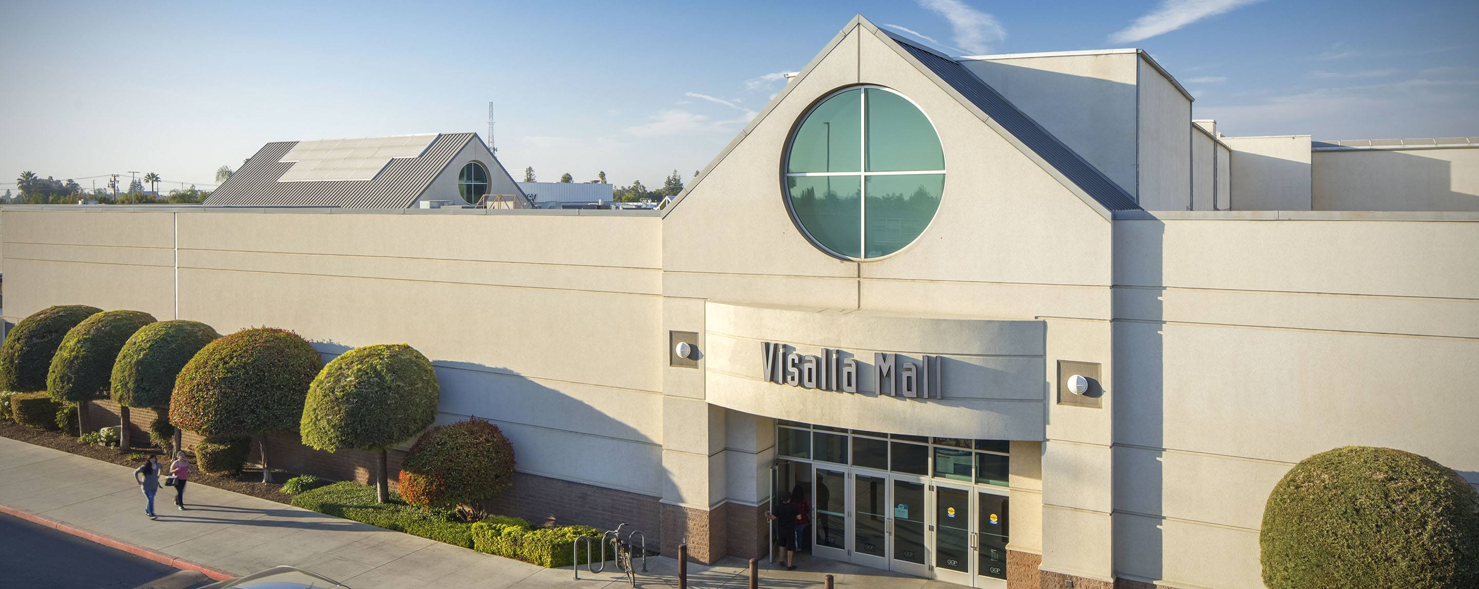 An exterior shot of the Visalia Mall. The building is landscaped with bushes and grass.