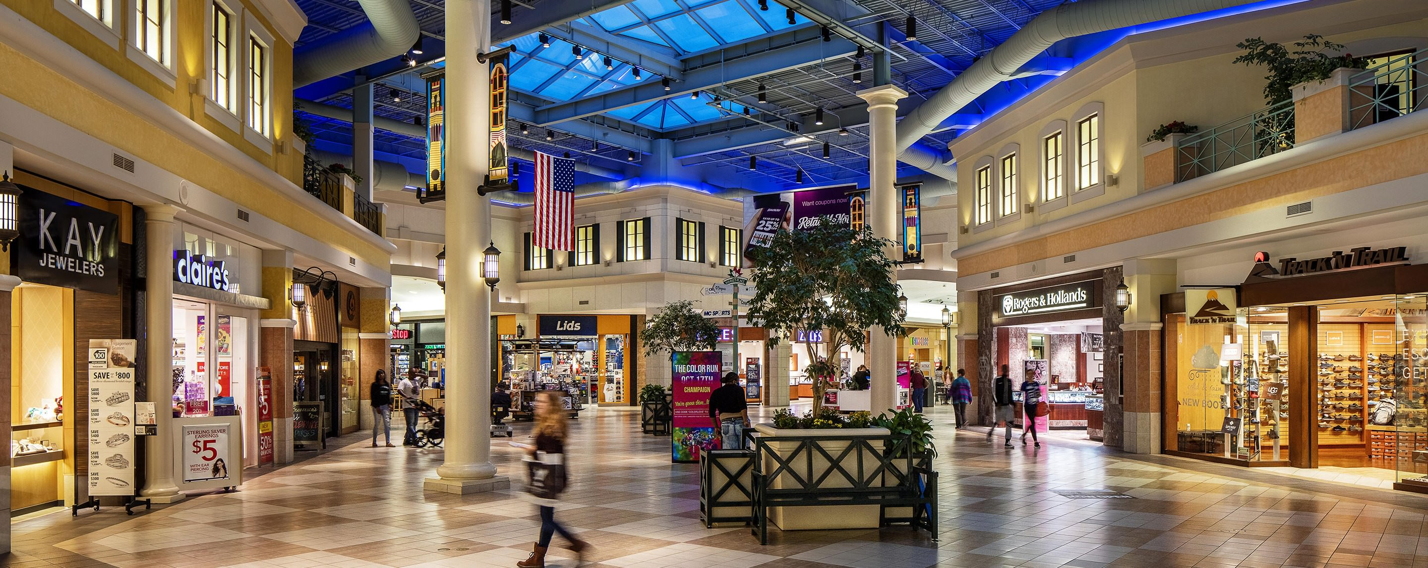 A variety of well lit storefronts line a multi-story mall, including Lids and Claire's.