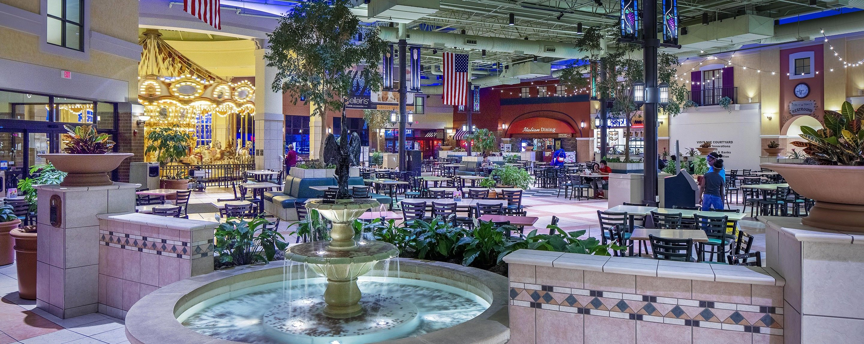 A fountain stands in front of a food court in an indoor mall. A carousel is lit in the background.