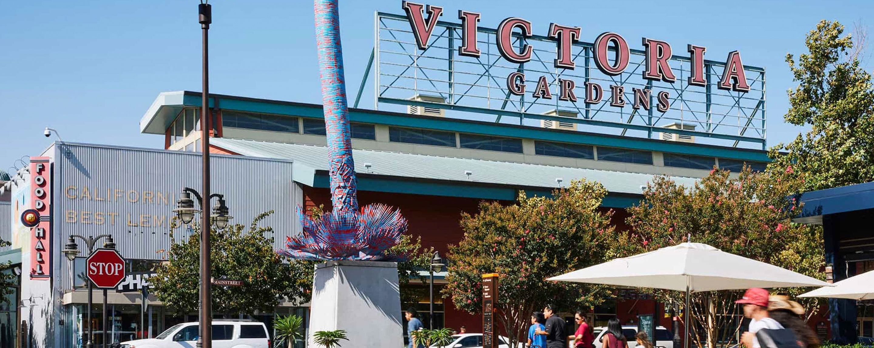 "A large red sign that reads ""Victoria Gardens"" stands above a large commercial building."