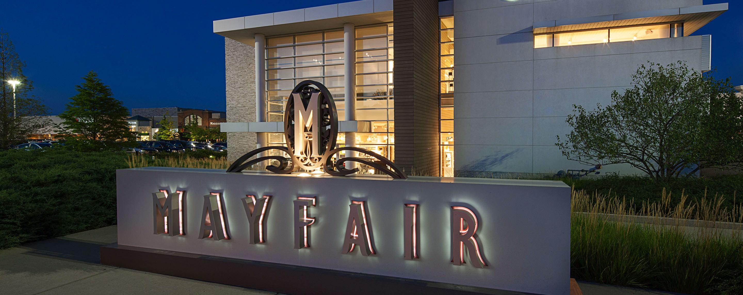 """A sign for an outdoor shopping plaza illuminating the word """"Mayfair"""" with backlit, embossed text in"""