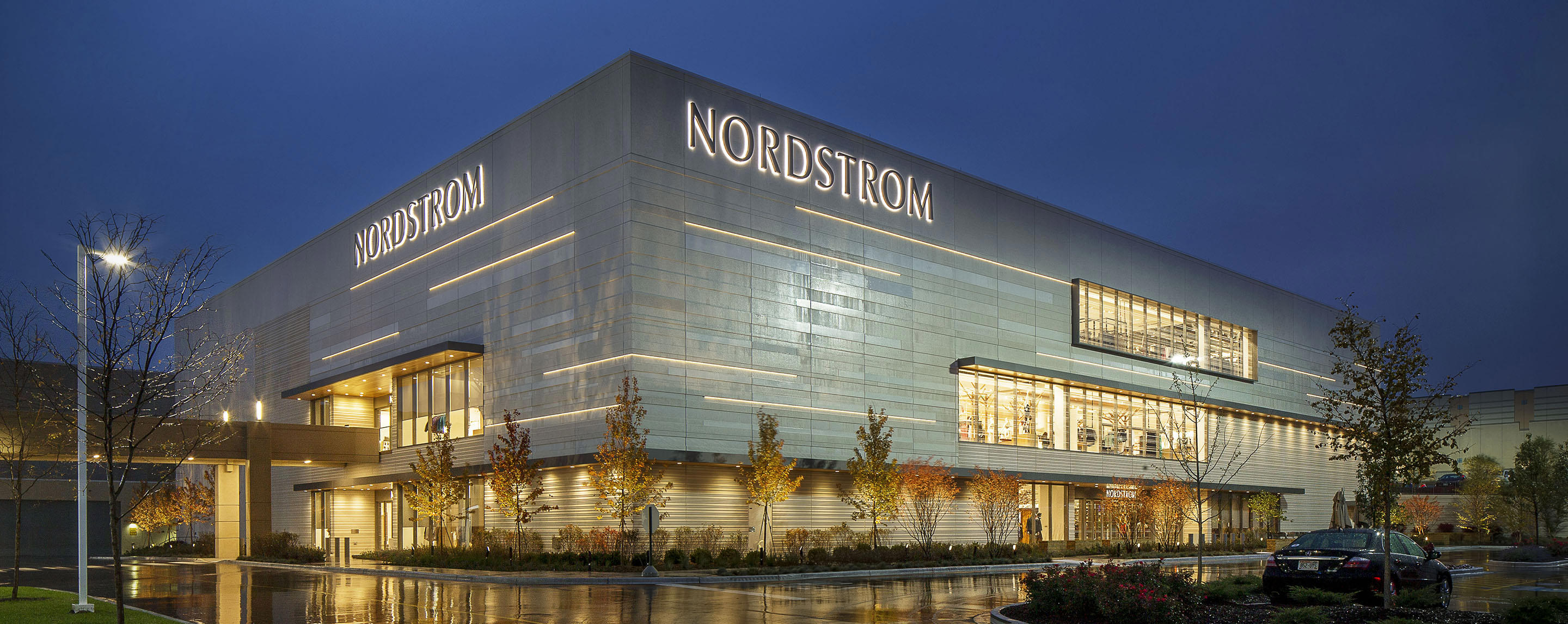 A Nordstrom shines brightly in the dusk, next to a single vehicle in its parking lot.