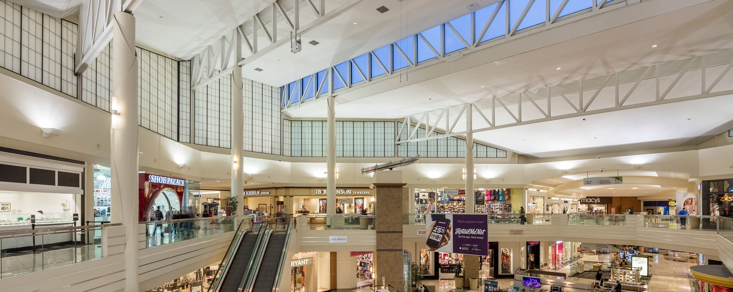 A large indoor mall has two floors and a couple of escalators leading to the top.  There is a large