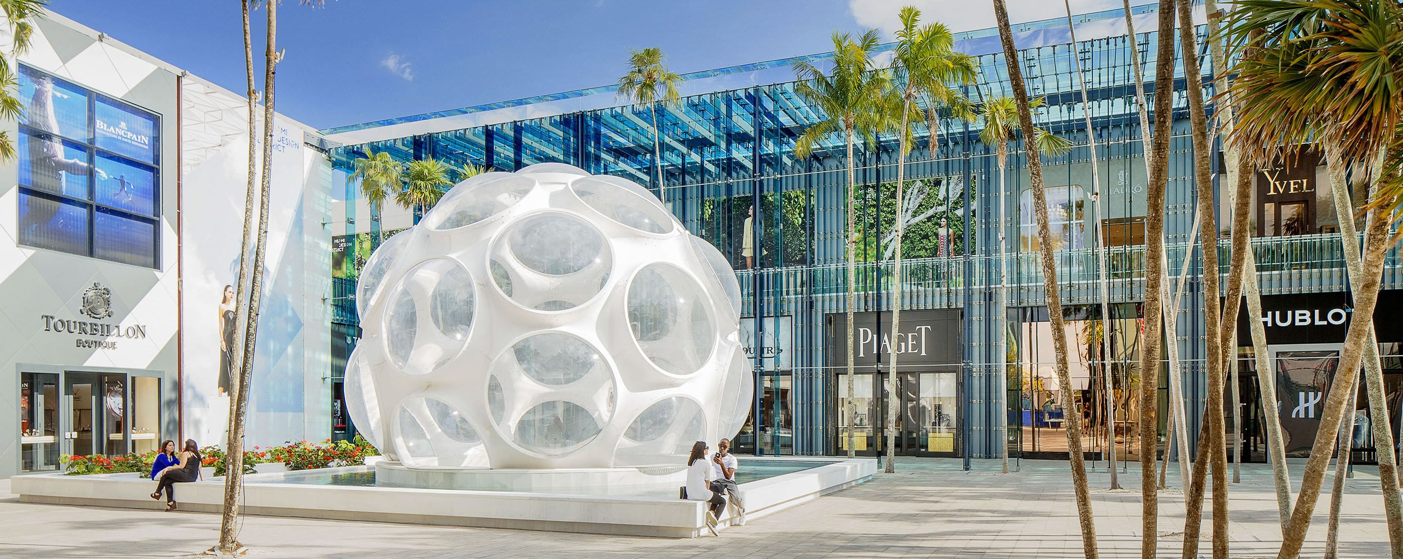 A large white sculpture stands outside of a glass-fronted mall on a sunny day. The store Tourbillon is visible.