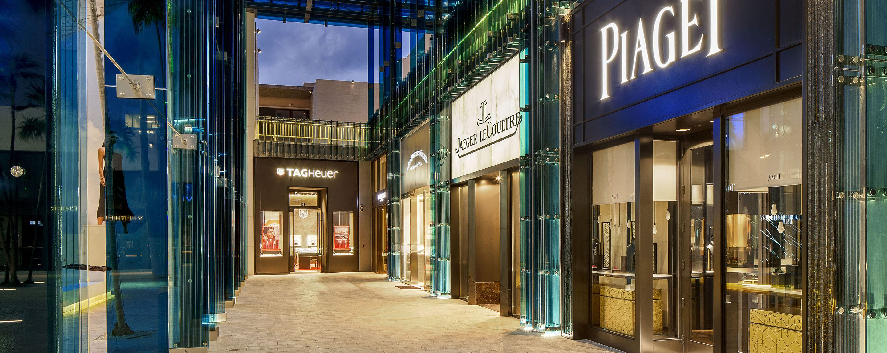 Several storefronts line a well lit indoor mall, including Piaget and Tag Heuer.