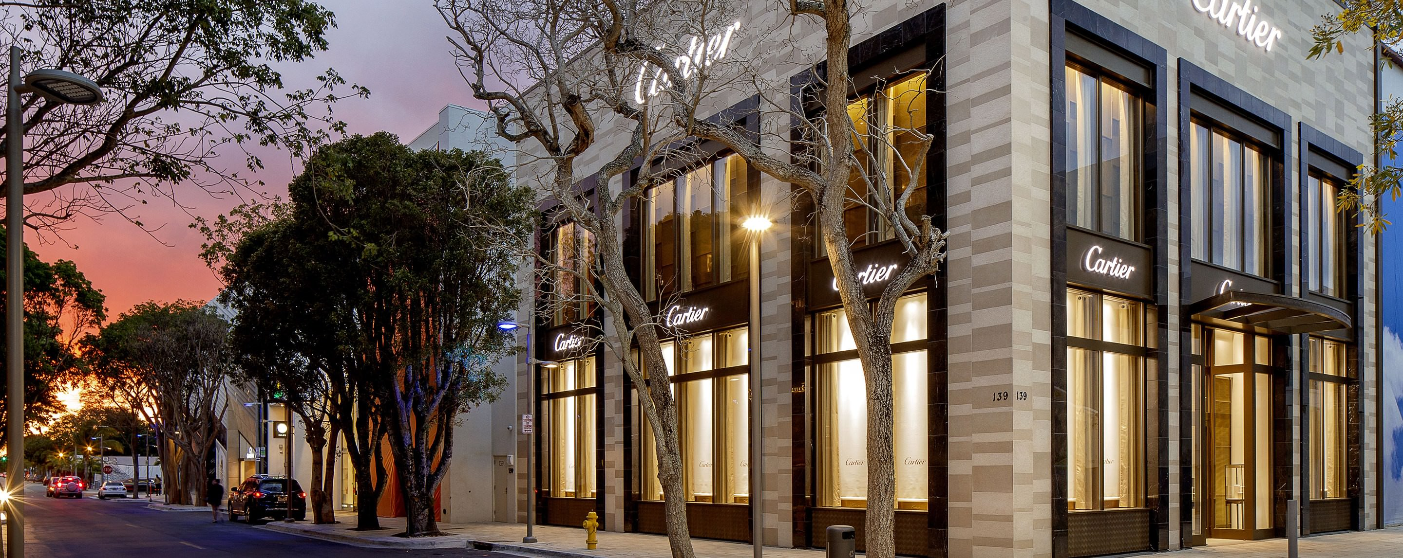A shot of the outside of a Cartier location. The building is brightly lit and the sun is setting.