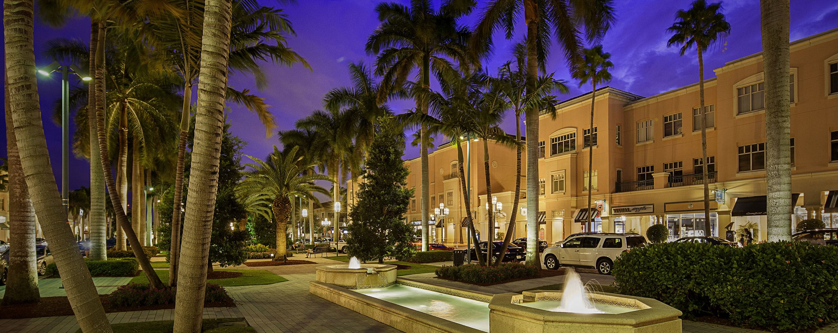 A large courtyard with several fountains and palm trees.