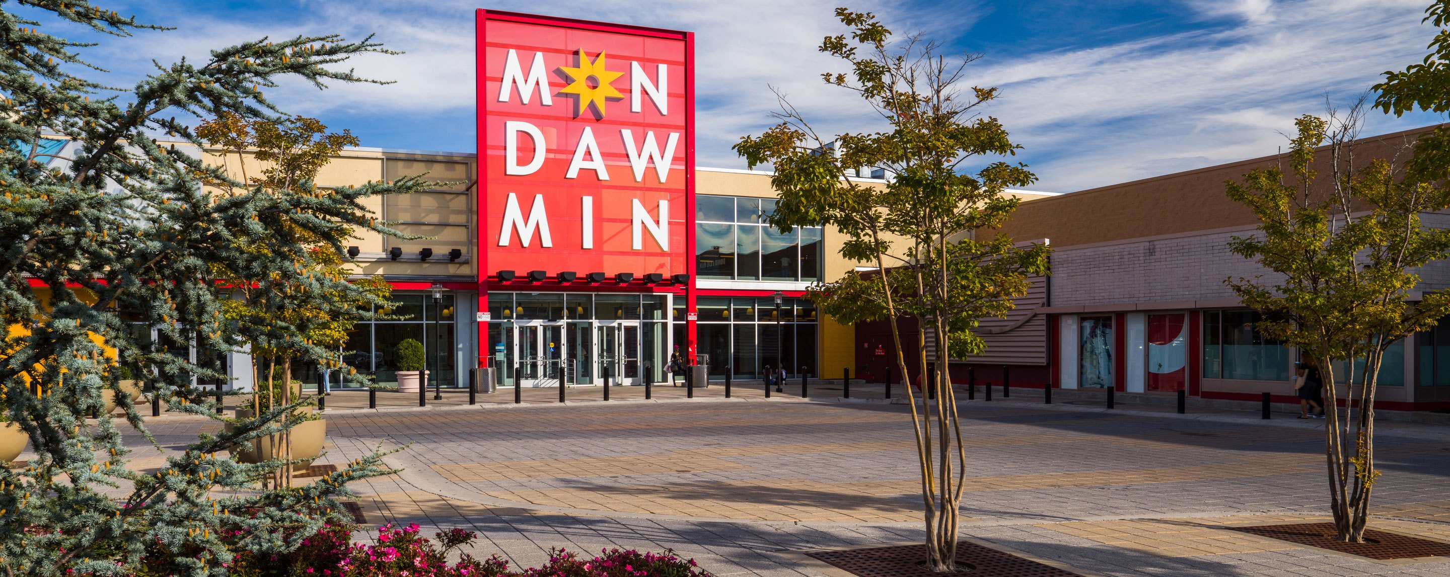 """A very large red sign reading """"Mondawmin"""" stands outside of a large two story building."""