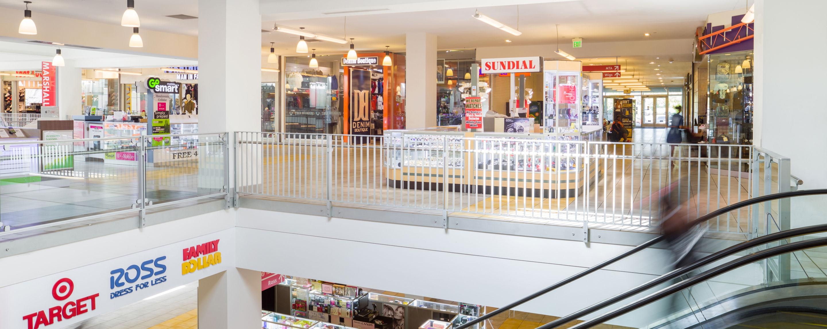 The shot from the top of an escalator in a two story mall. A Sundial stand is directly in front of the camera.