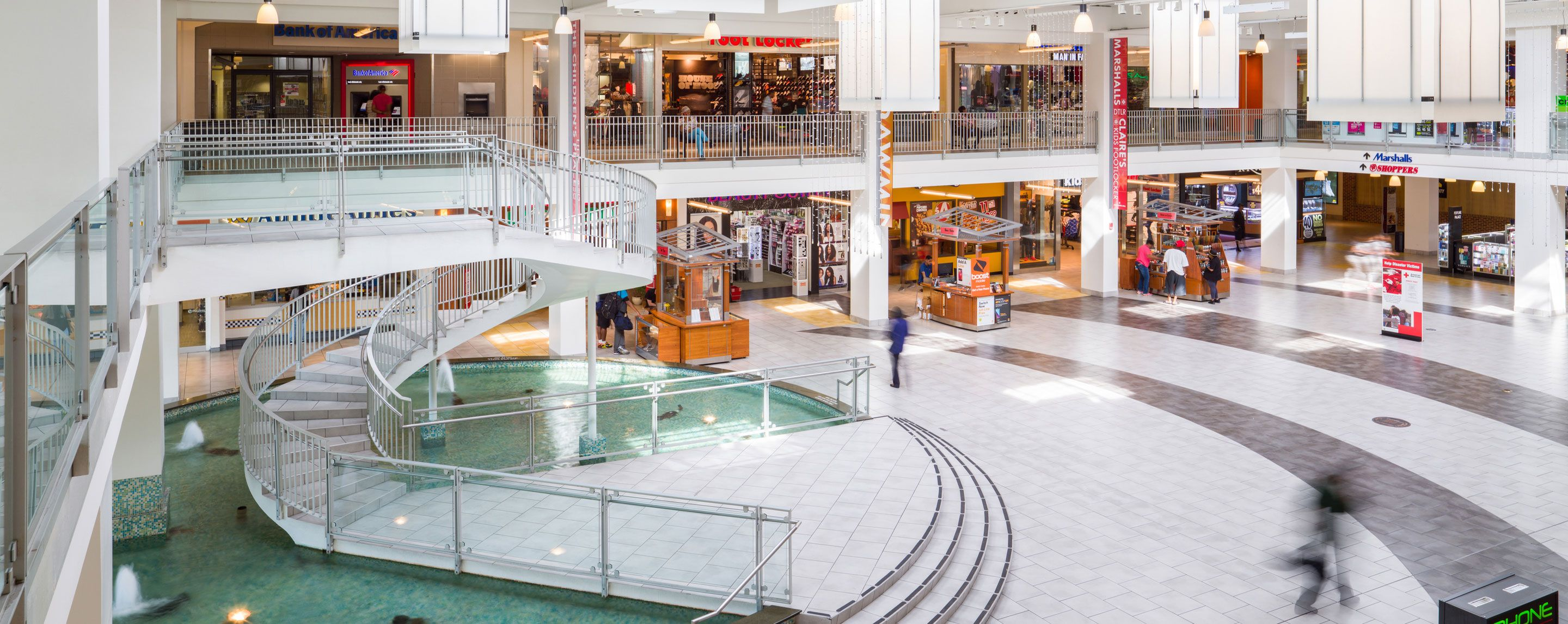 A large shopping mall with 2 floors and a spiral staircase.