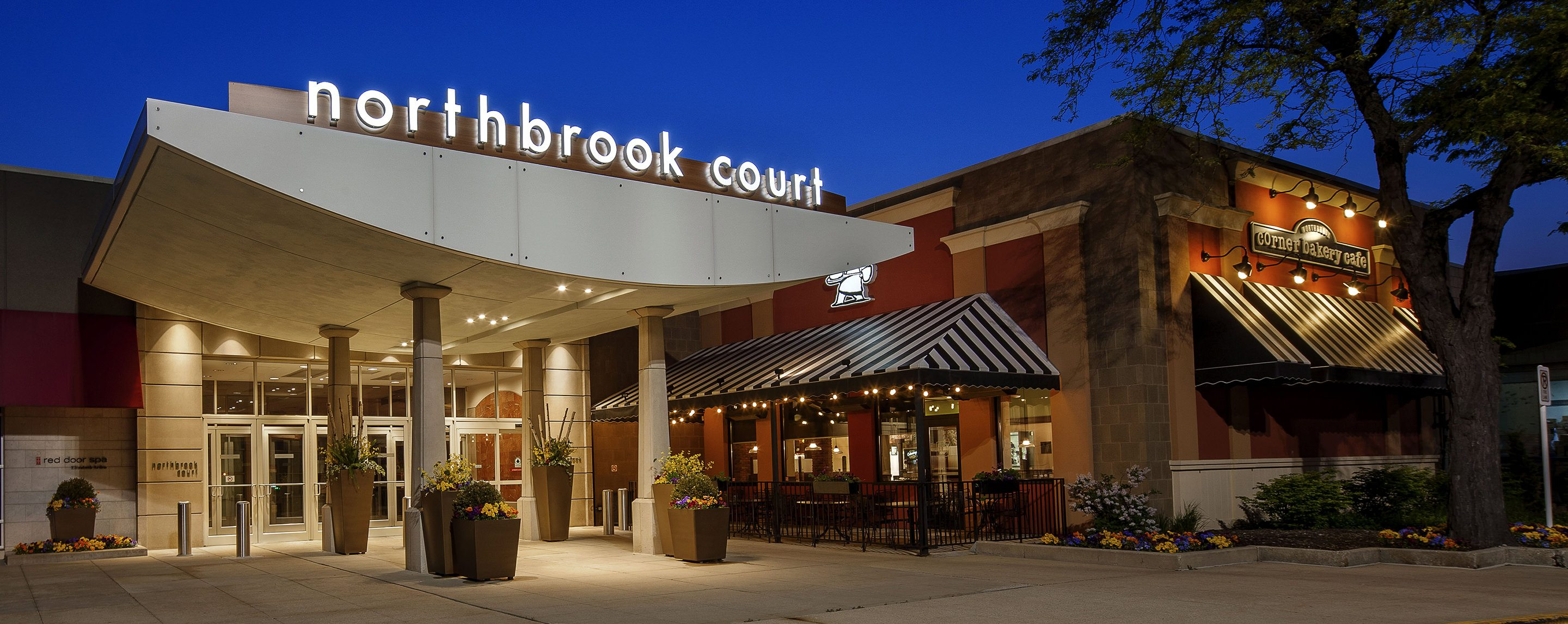 The sign to the Northbrook Court is lit up outside of the Corner Bakery Cafe store.
