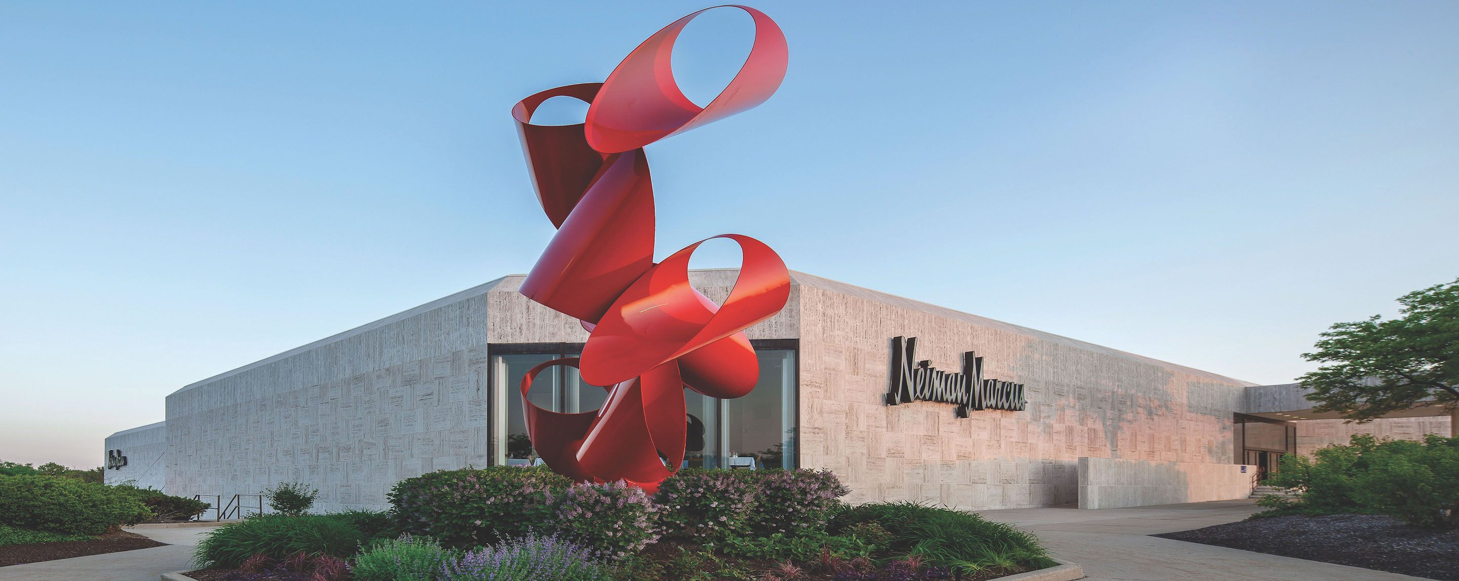 A large red statue is in front of a Neiman Marcus.