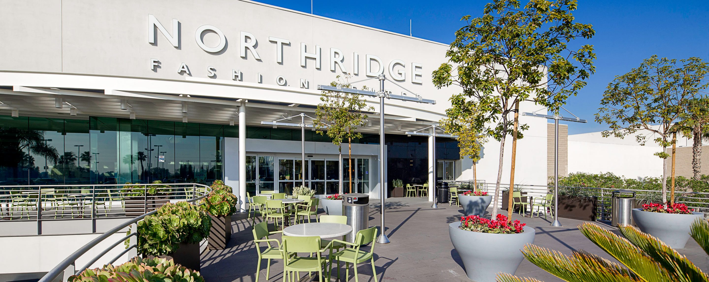 An exterior shot of the Northridge Fashion Center. Palm trees and chairs are visible.
