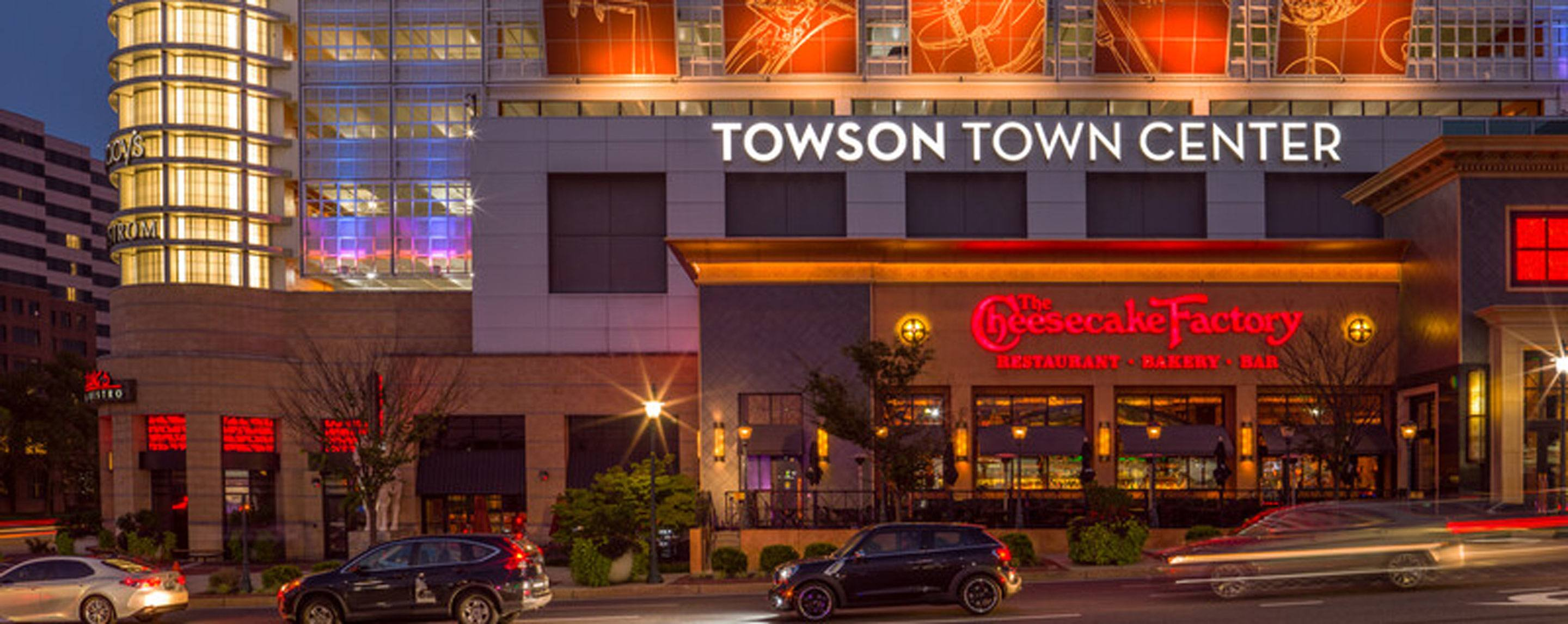 Cheesecake Factory's red sign is illuminated underneath the sign for the Townson Town Center at twil