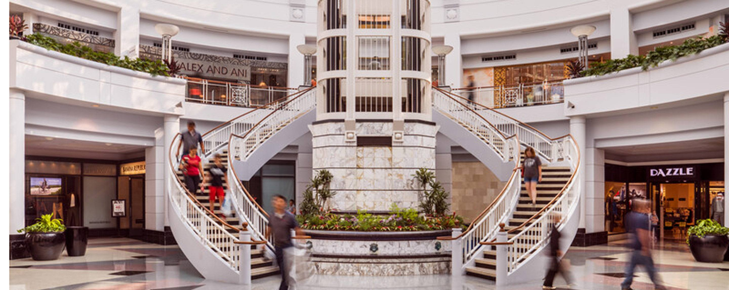 A double staircase leads upstairs in a mall. Storefronts including Dazzle and Alex and Ani are visible