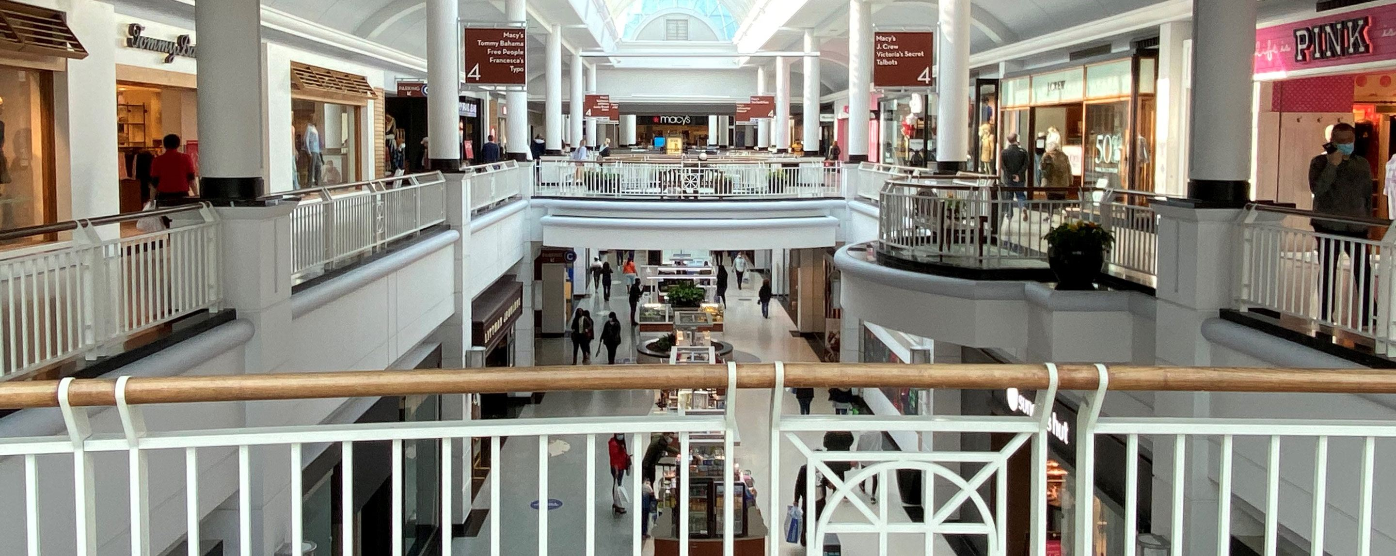 Overlooking the balcony on the second floor of an indoor mall near PINK, Tommy Bahama, and in the Macy's wing.