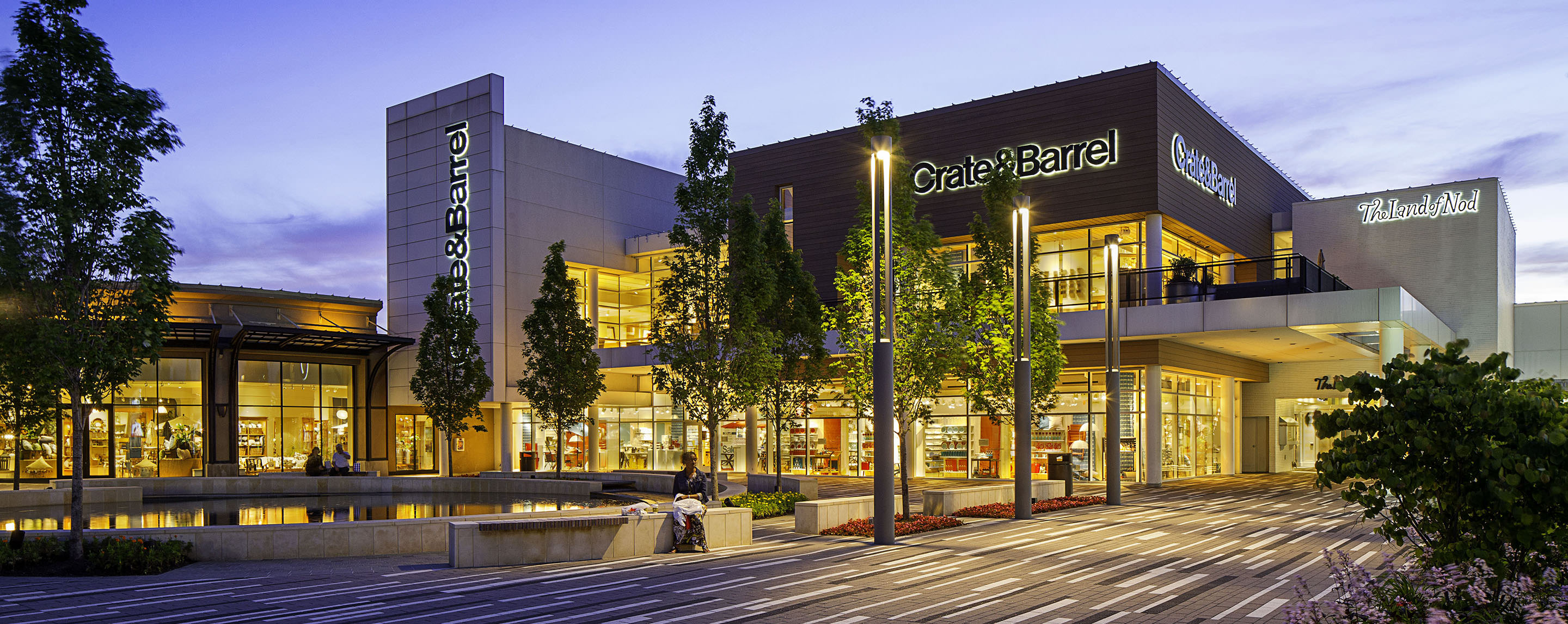 An exterior shot of a Crate and Barrel location. A customer sits outside on the edge of a fountain