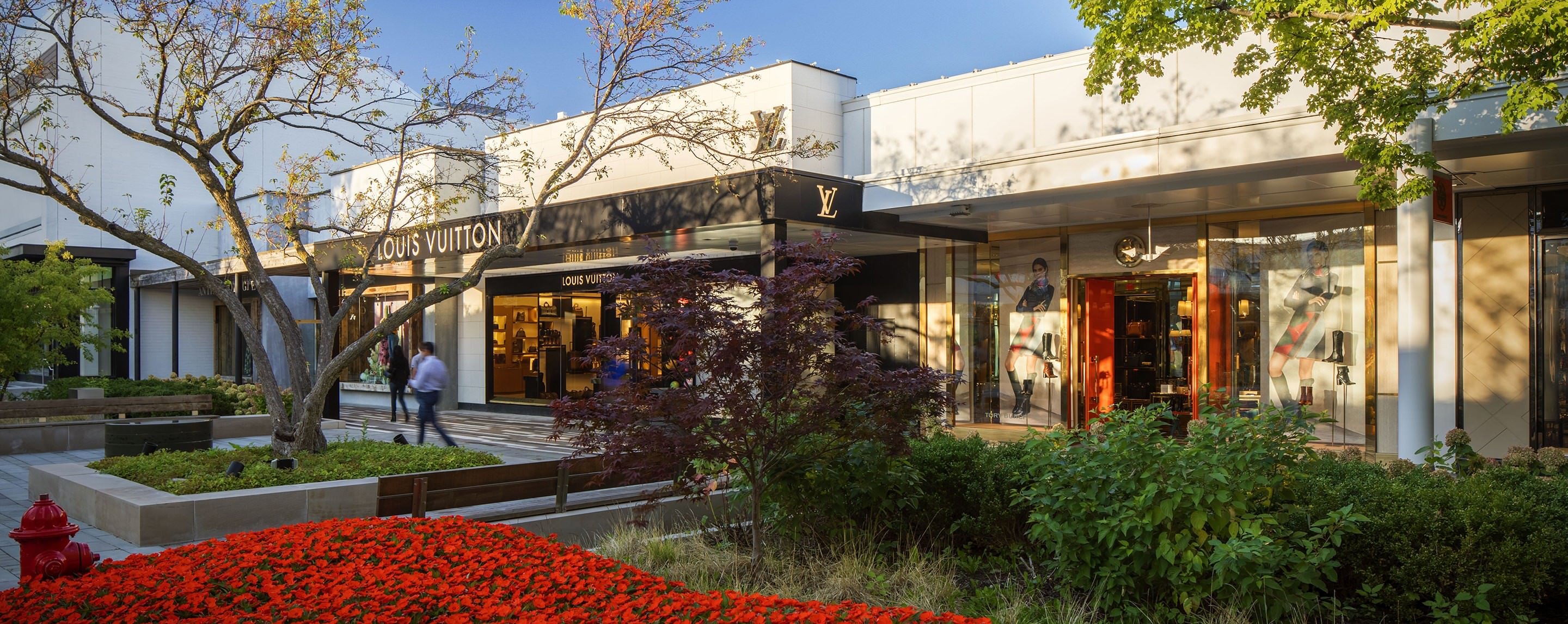 A building that says Louis Vuitton with trees and red flowers in front.