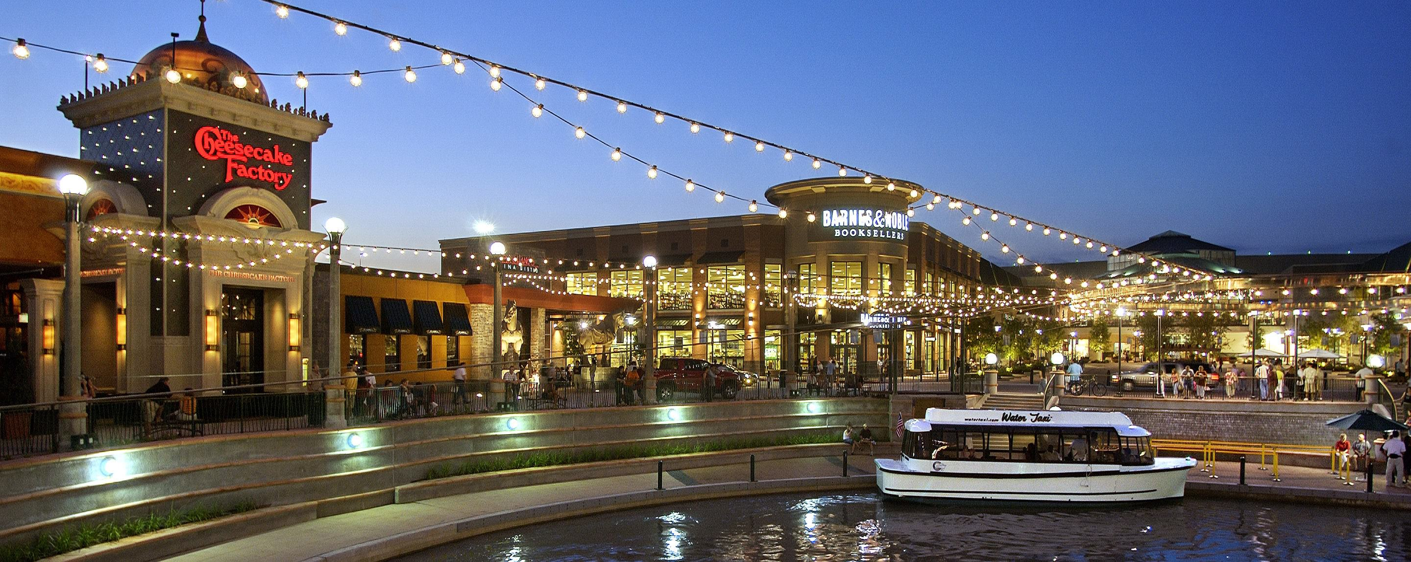 A small boat is docked in the water in front of a large mall featuring a Cheesecake Factory, a Barne