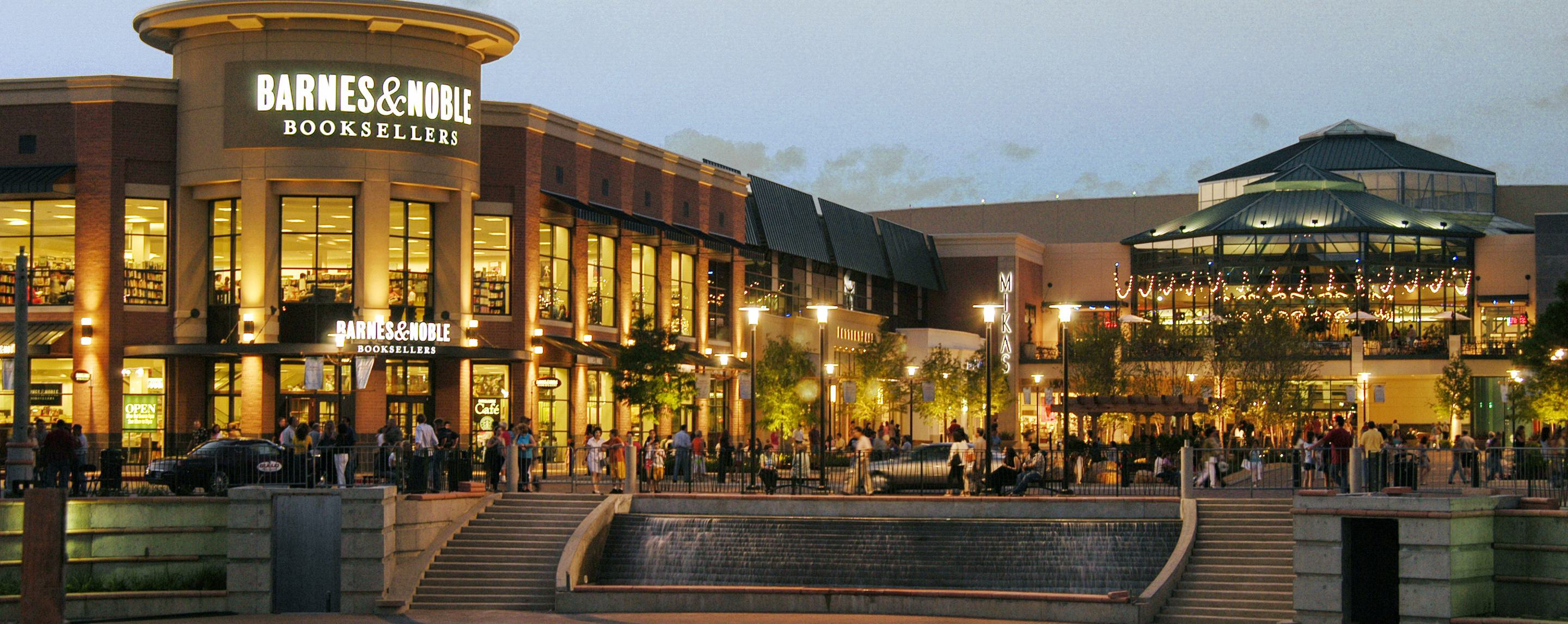 People walk around on the sidewalk near a Barnes and Noble store in a shopping center at dusk.