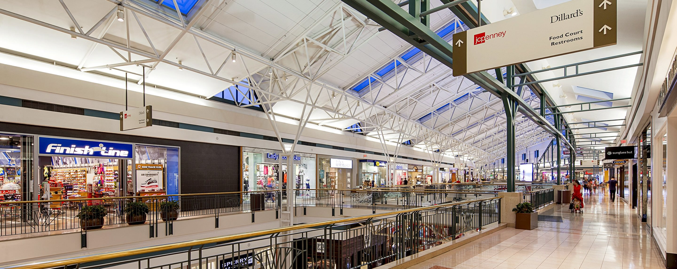 Stores such as Fossil, JCPenney, Dillard's, and Sunglass Hut are located in a shopping center with two levels.