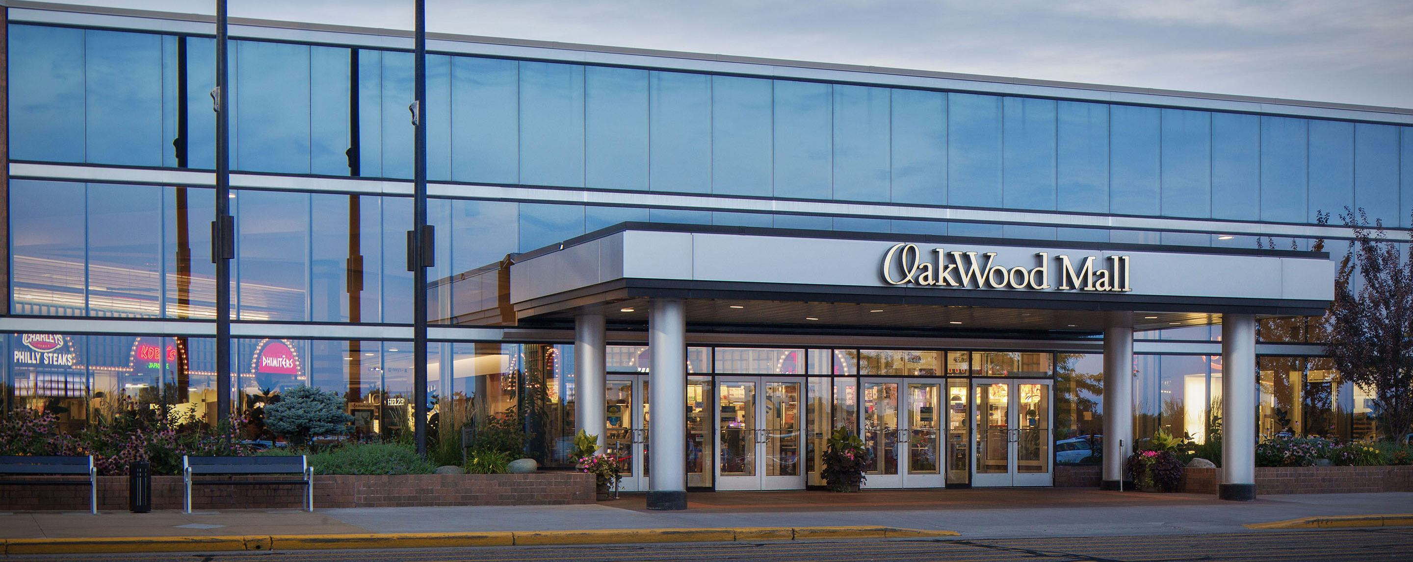 An outside shot of the Oakwood Mall. A three story glass wall rises behind the lit sign.