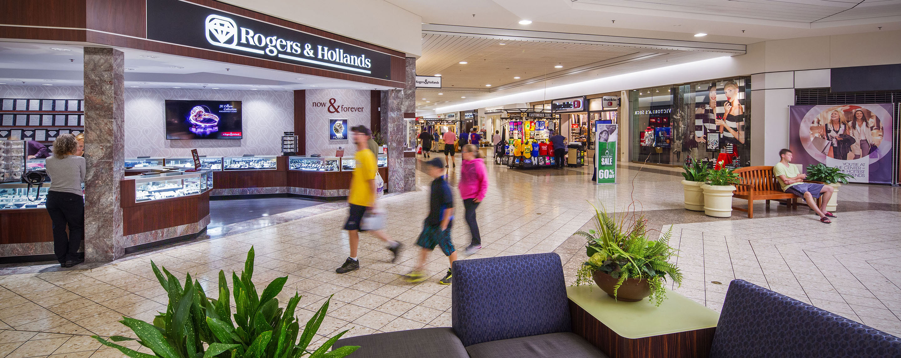 A group of people are walking in an indoor mall towards a Rogers & Hollands store.