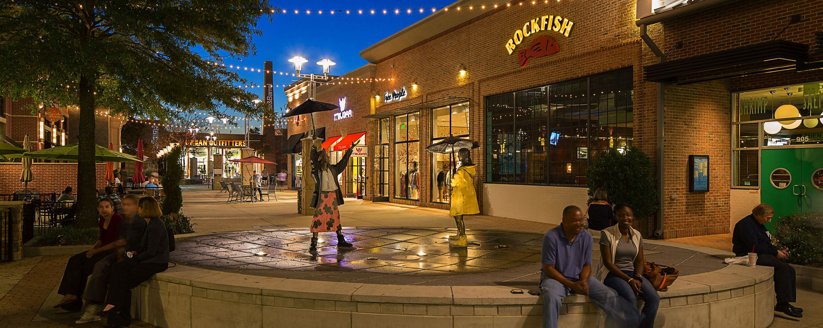People sit and stand near a water feature outside of a stores near a shopping center.