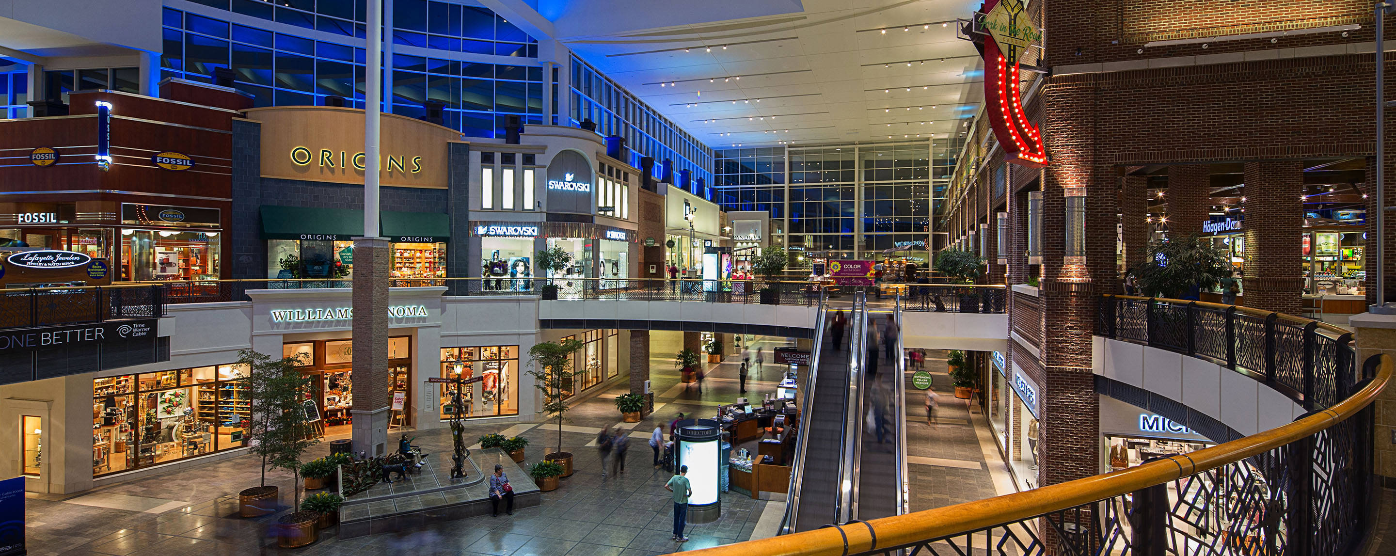 A windowed shopping center with escalators hosts a Fossil, Origins, Swarovski and a Jewelry repair store.