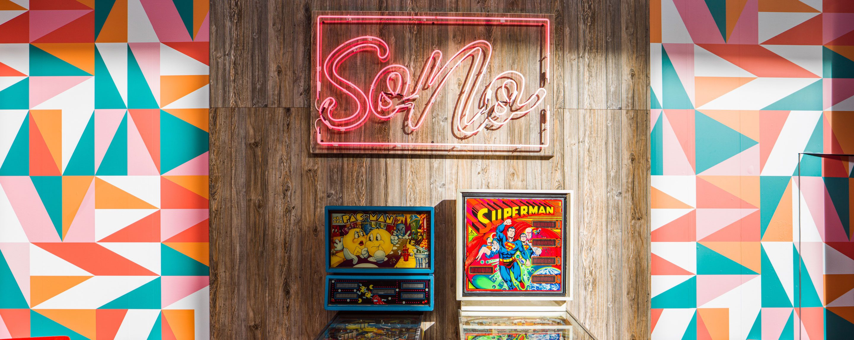A Pac-Man and Superman pinball game are placed against a wood wall below a neon sign.
