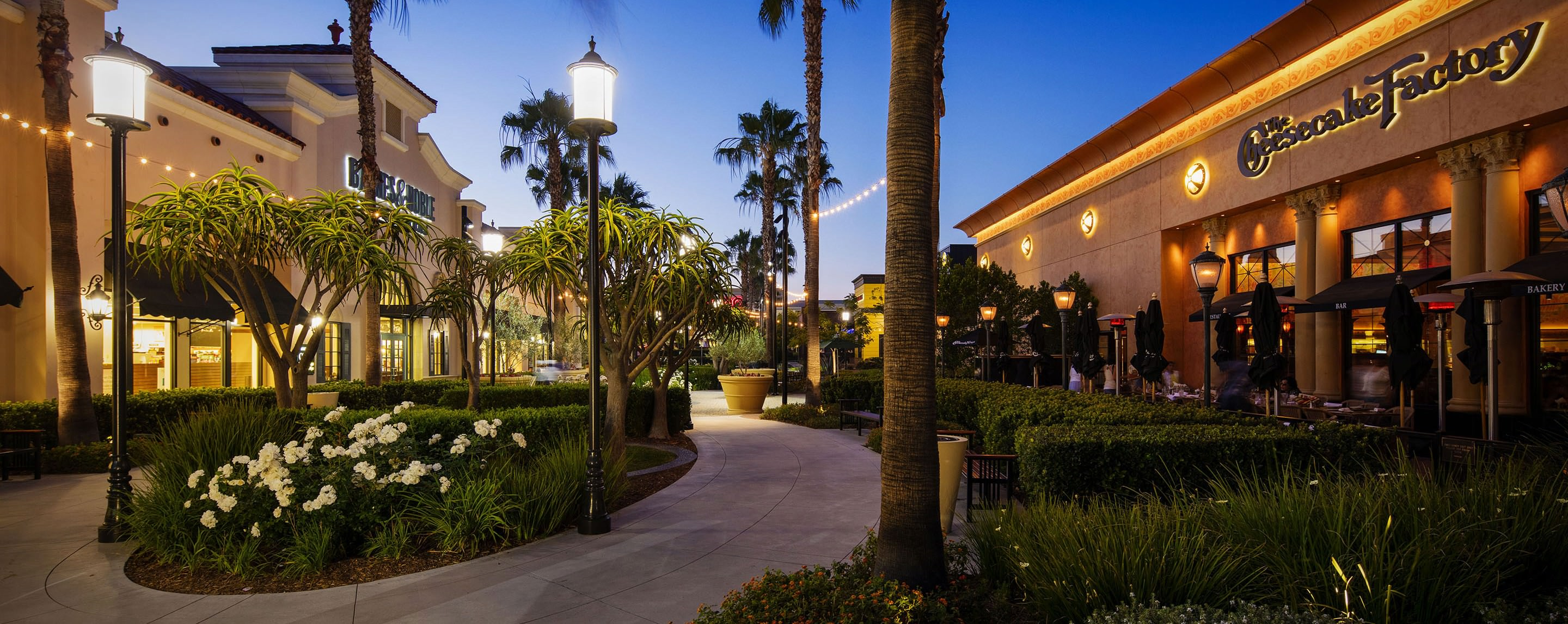 An outside shot of the landscaping between two buildings. One of the buildings is a Cheesecake Factory.