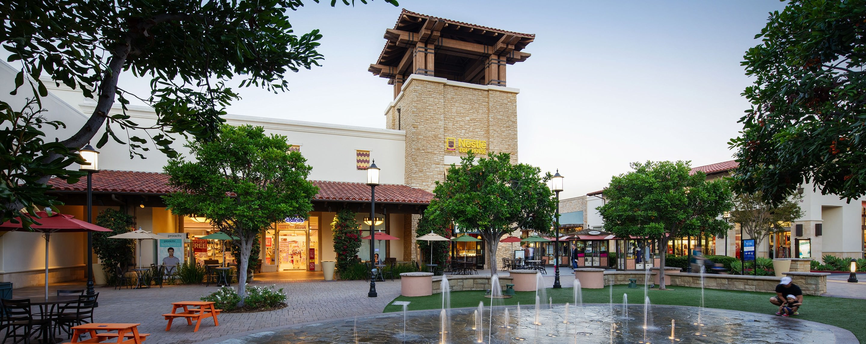 A fountain in an outdoor shopping plaza near a Claire's jewelry store and a Nestle Toll House cookie shop.
