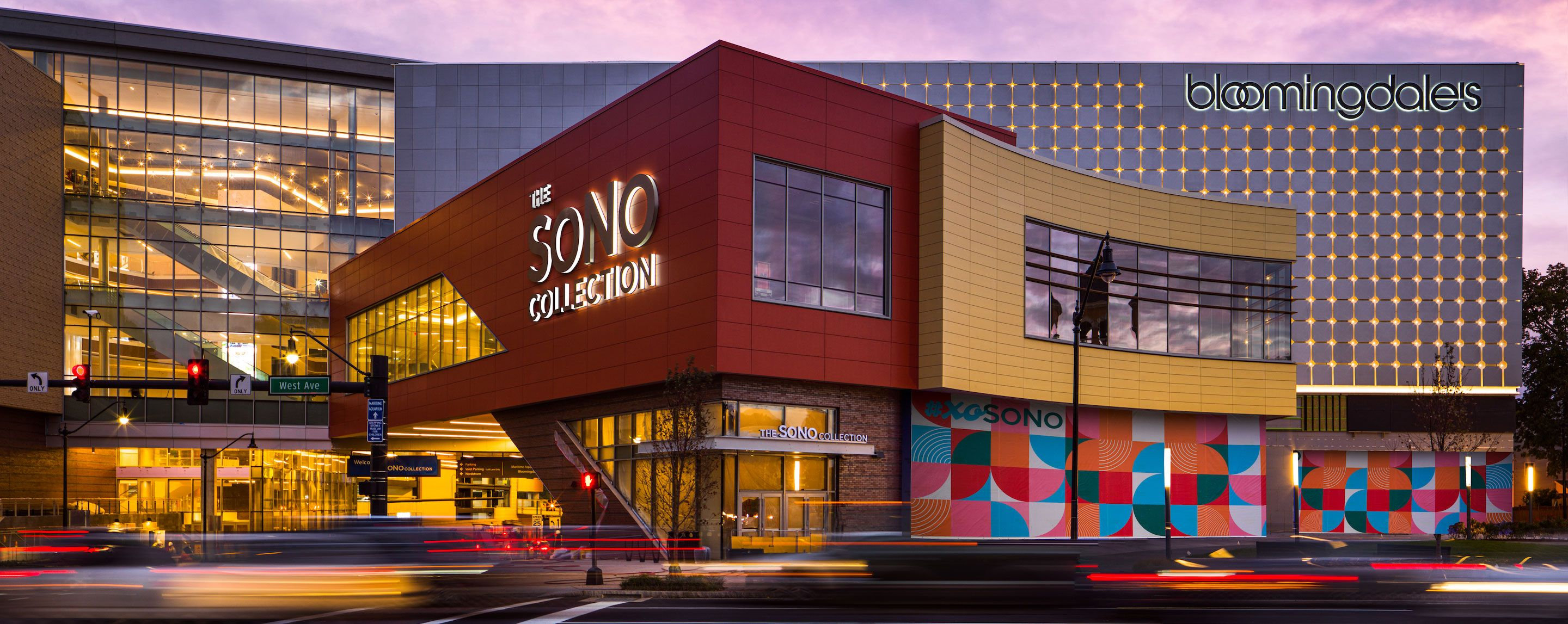 A two storied building with the words The SONO Collection stands near a larger building housing the Bloomingdale store.